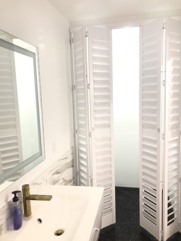 Norman clear view bi-fold shutters for a new modern bathroom.